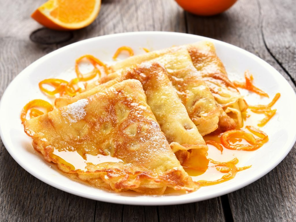 Crepes Suzette on white plate over wooden background