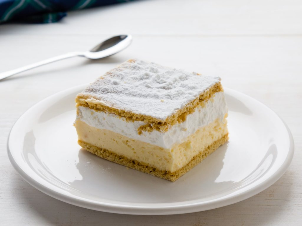 Cream pie with layers of puff pastry on white table