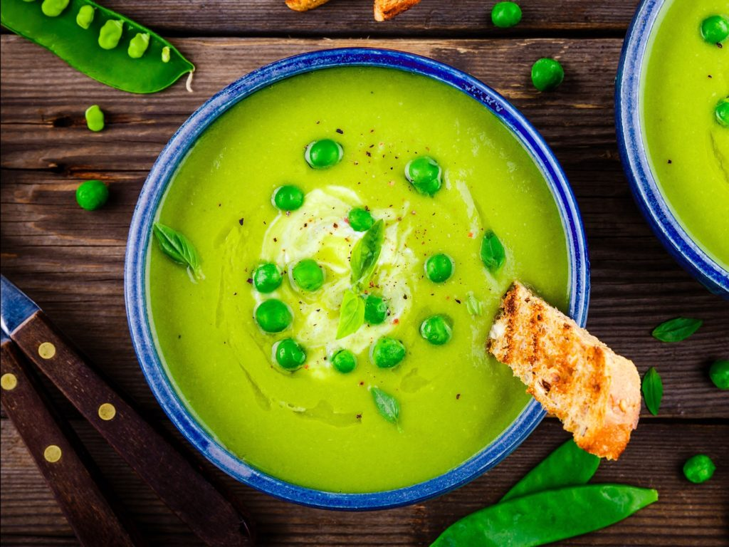 Green pea soup with croutons on wooden rustic background
