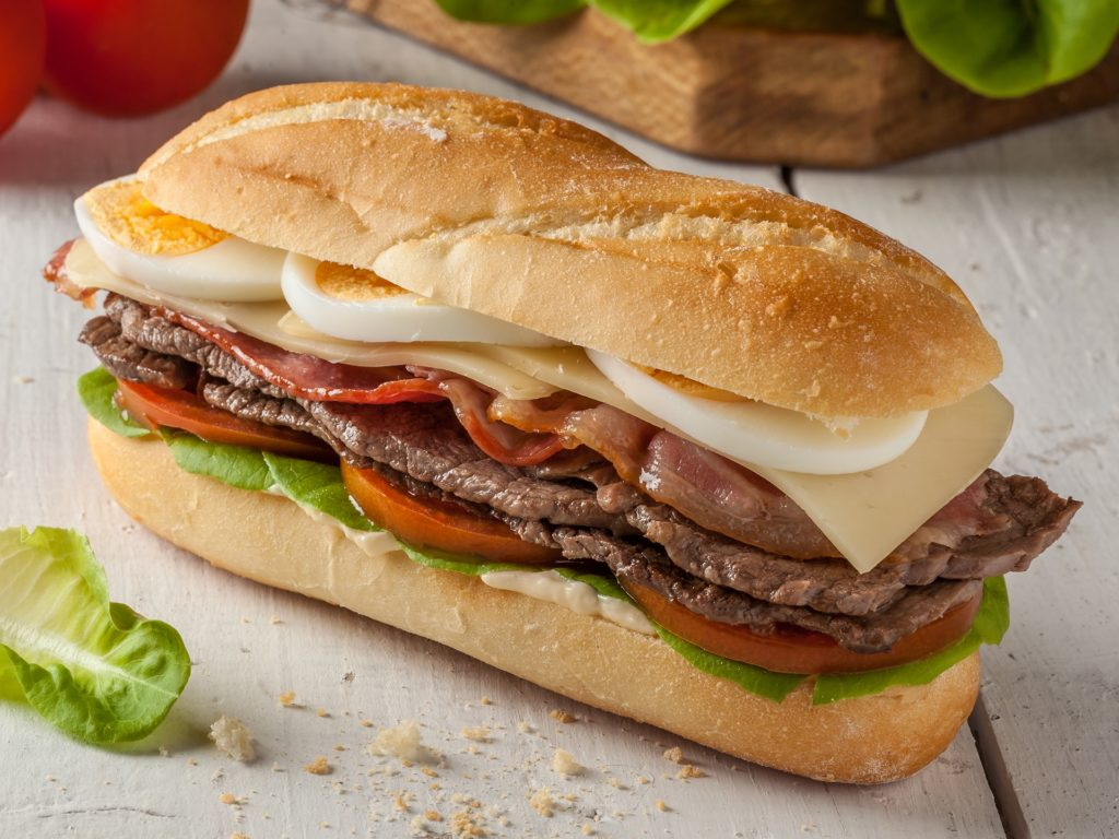 Chivito is a typical sandwich from Uruguay, with lettuce, tomato, bacon, beef, fried or boiled eggs and cheese.