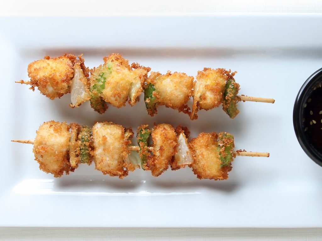 Fried Chicken Kushi sticks with onion and green pepper with dipping sauce.