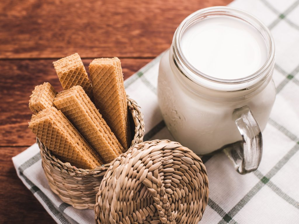 Milk and wafer on wooden background. Concept for break time, morning lifestyle, breakfast.