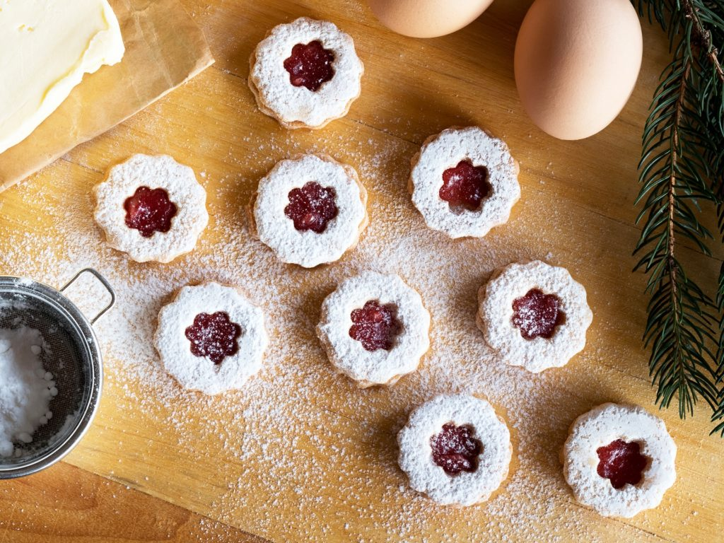 Preparation of traditional Linzer Christmas cookies, top view. Christmas cookies, butter, eggs and sugar on a wooden table.