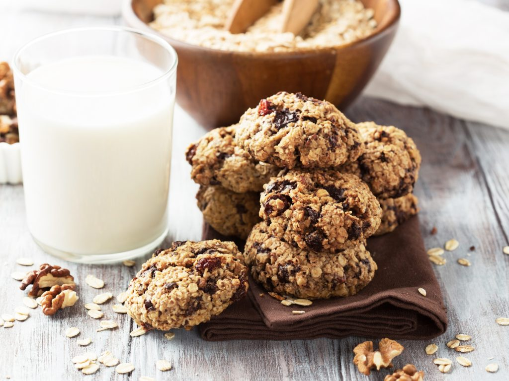 Homemade crunchy oatmeal cookies with dark chocolate and a glass of milk on a white wooden background, selective focus