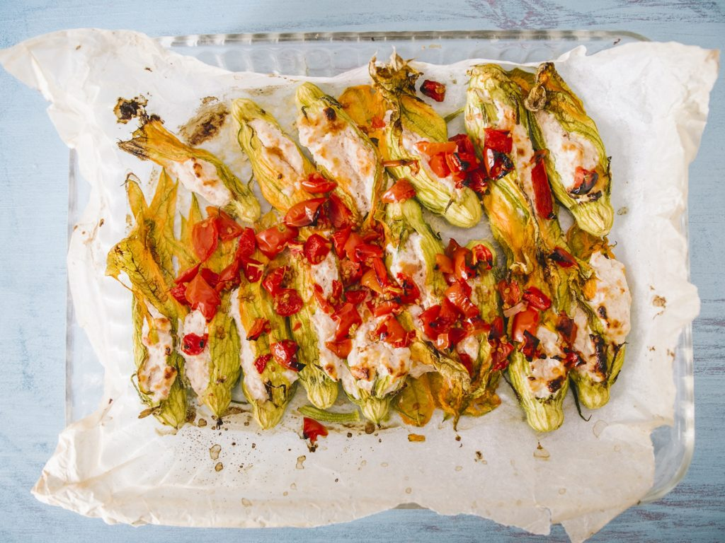 Stuffed courgette flowers with ricotta cheese, baked in oven with tomatoes and presented over cook paper, on a rusty blue light background.