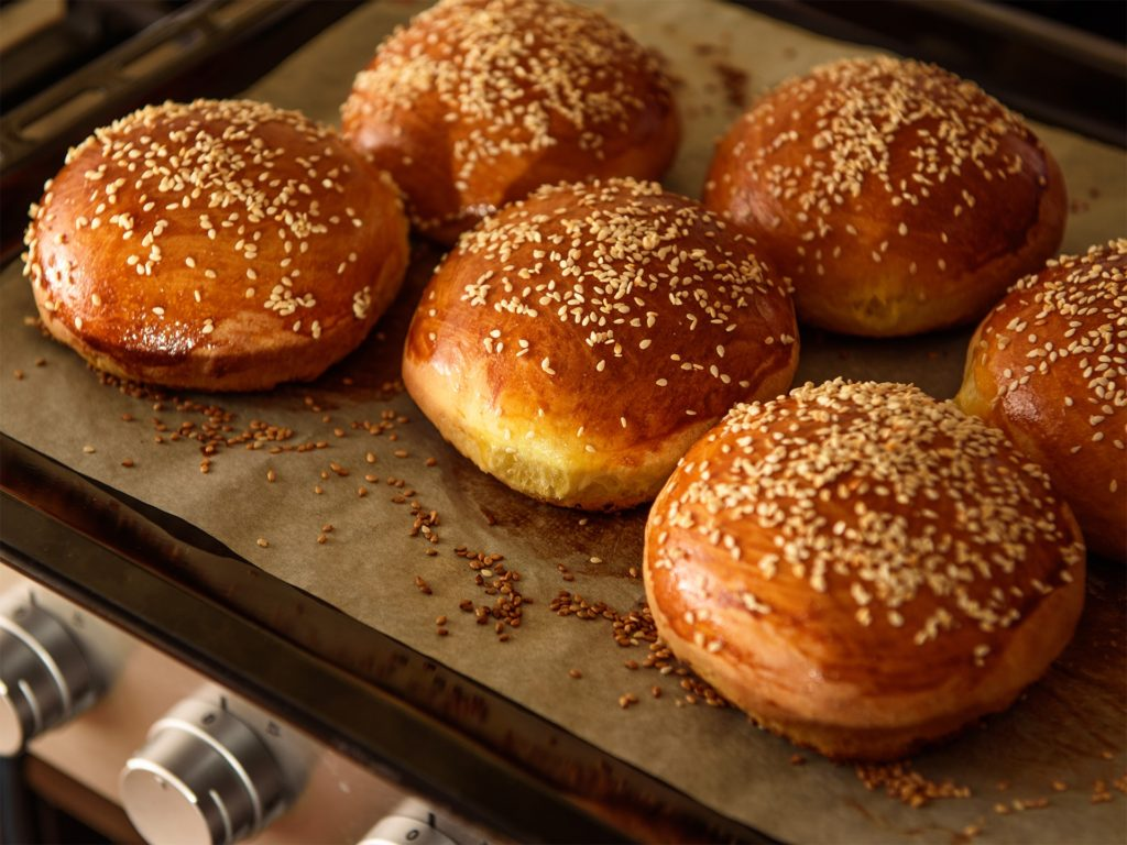 homemade burger rolls sprinkled with sesame seeds are baked in the oven