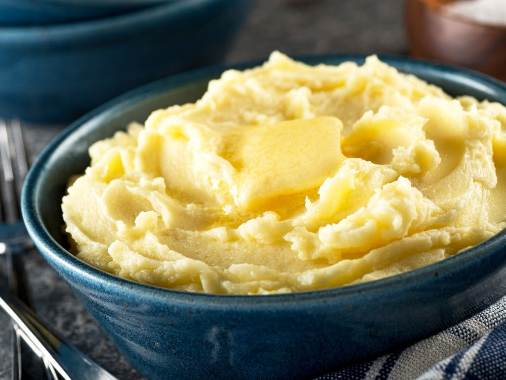 A bowl of delicious mashed potatoes with melted butter.
