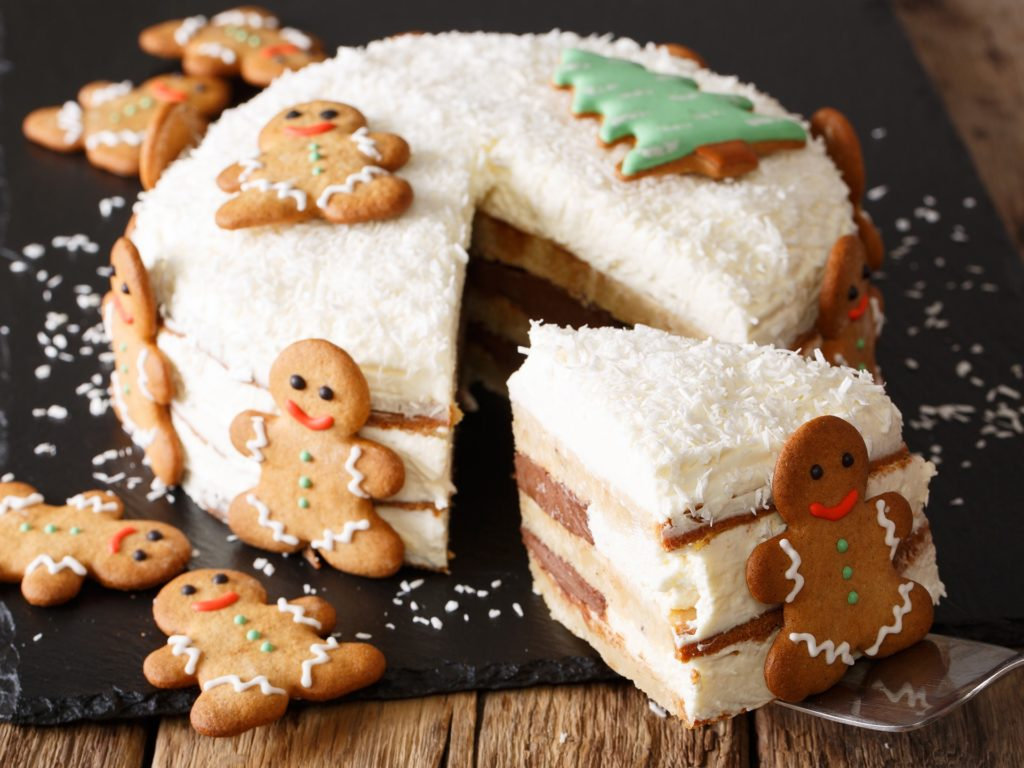 piece of Christmas cake with cheese cream is decorated with gingerbread close-up on the table. horizontal