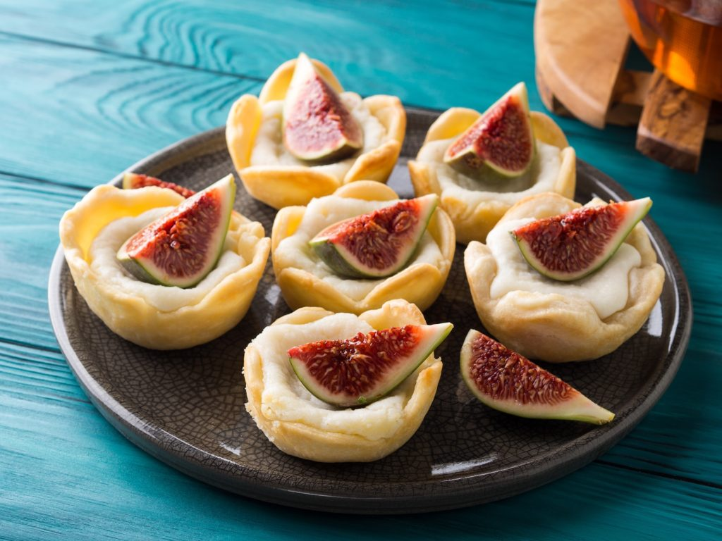 Tartlets with ricotta and figs on green wooden table. Mini treats