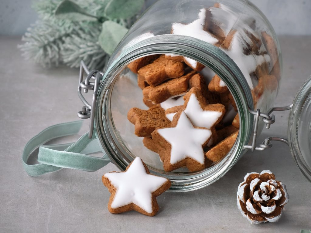 Christmas background with tasty star ginger cookies in a glass jar with winter decorations, copy-space