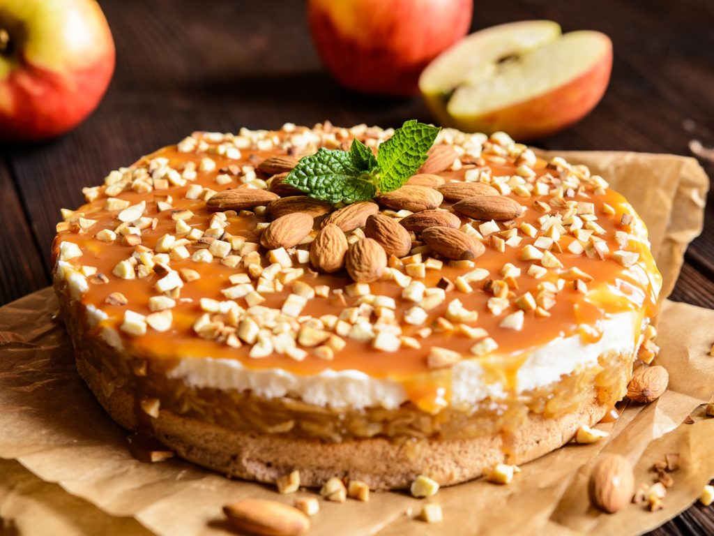 Delicious cake with apple and whipped cream filling, topped with caramel and almond