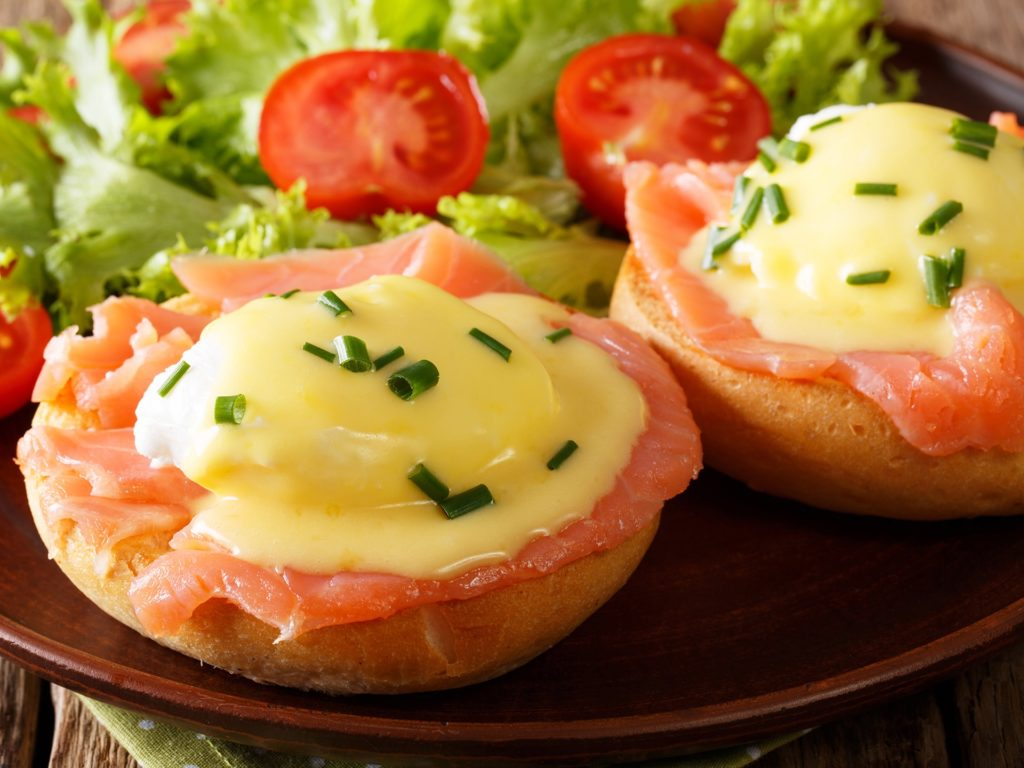 poached eggs with smoked salmon, hollandaise sauce and fresh vegetables close-up on a plate. horizontal