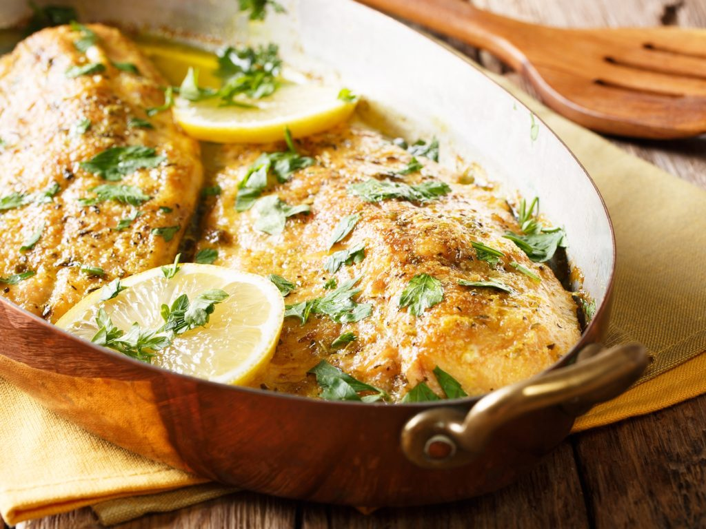 Delicious fish: baked trout fillets with garlic buttery herb sauce, lemon and parsley close-up in a copper frying pan. horizontal