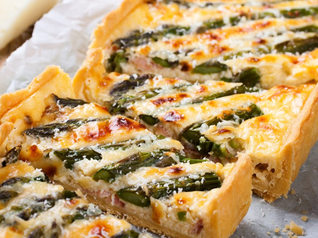 Delicious home made asparagus savory tart with pecorino and bacon on old wooden background. Selective focus.