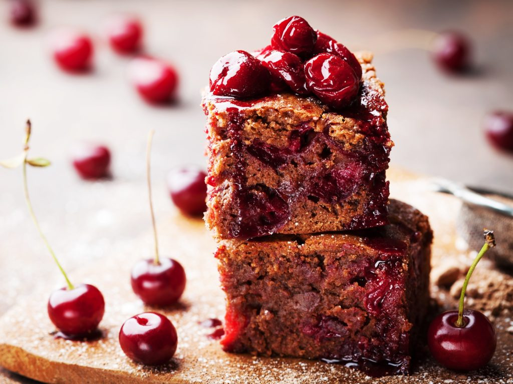 Chocolate brownie decorated with cherry. Homemade cake on wooden table. Macro.