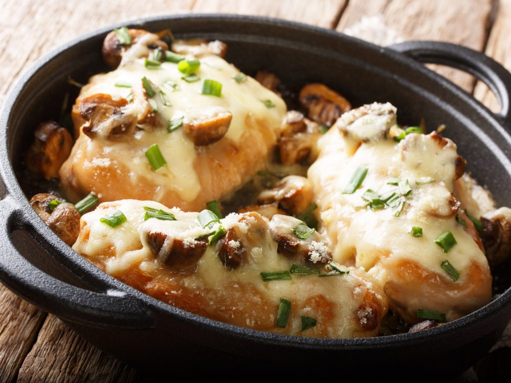 Lombardy Chicken breasts cooked with mushrooms, green onions, mozzarella cheese and parmesan closeup in a pan on the table. horizontal