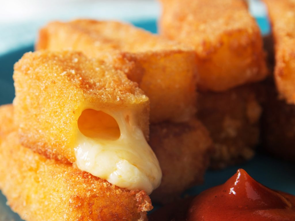 Vertical photo of fried cheese sticks with sauce