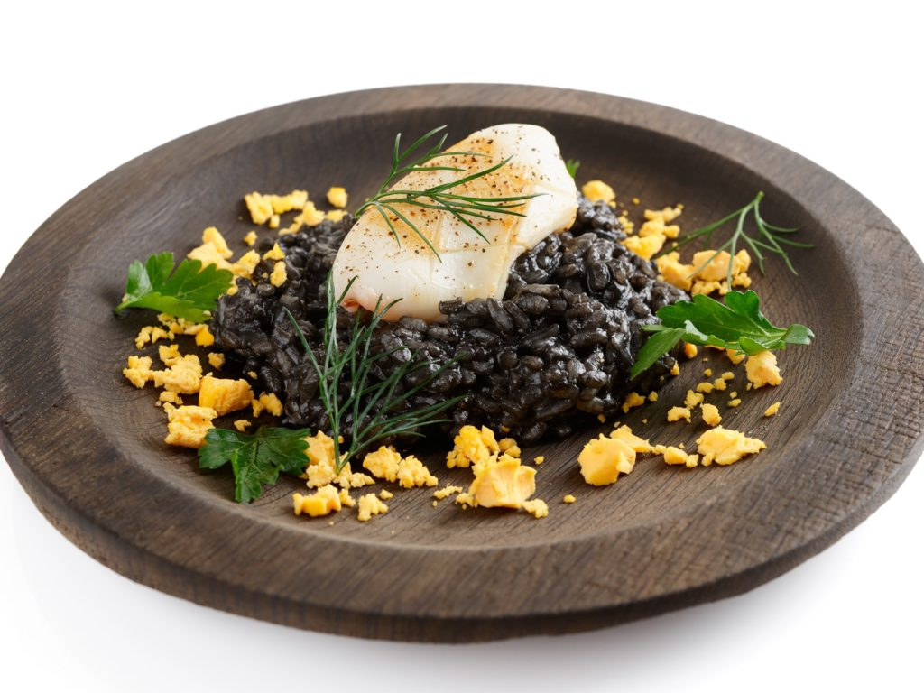 Black squid ink risotto with fried calamari in wooden plate, isolated on white