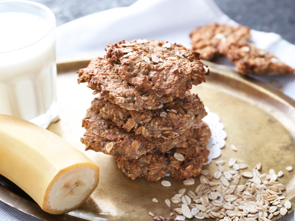 Plate with delicious oatmeal cookies and banana on table, closeup