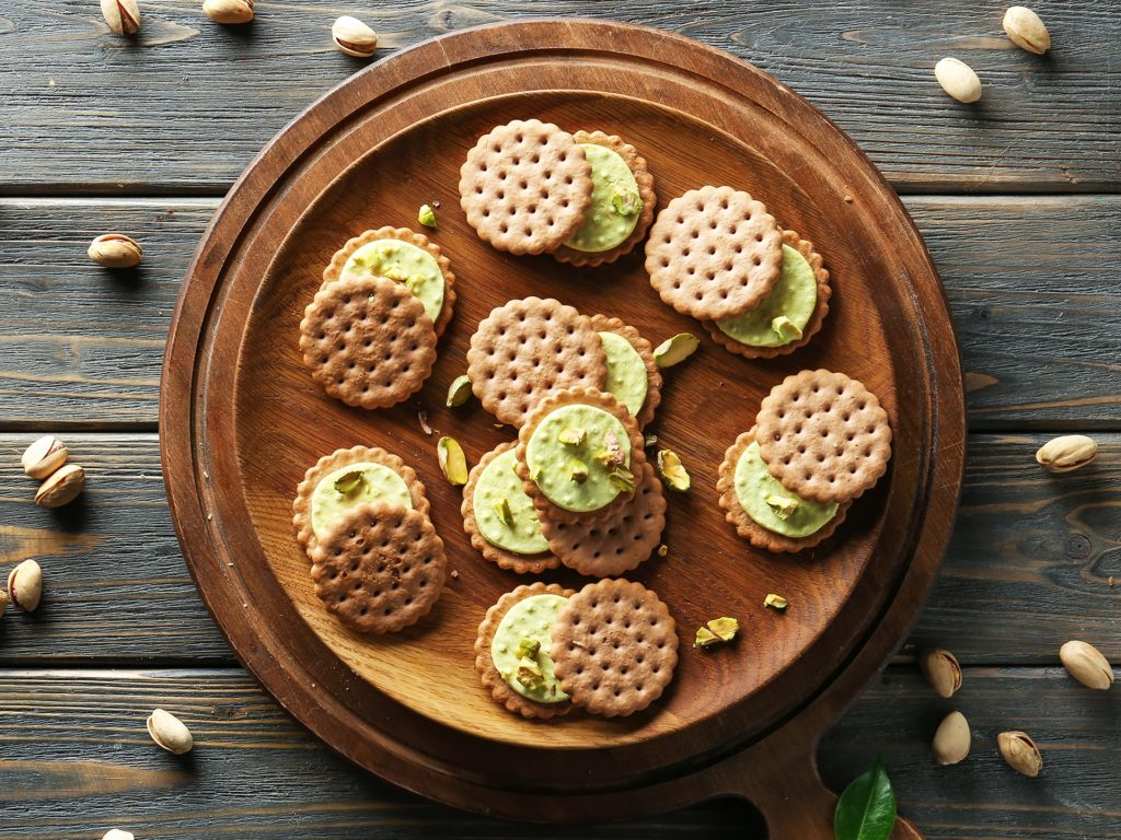 Plate with tasty pistachio cookies on wooden table