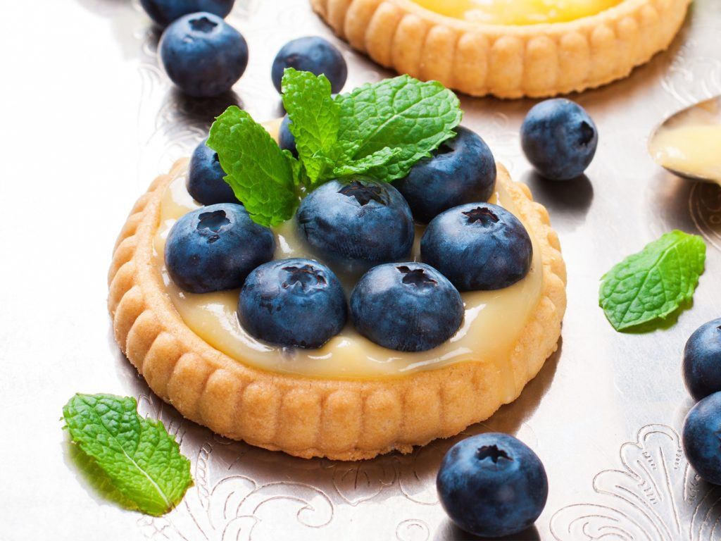 Process of making shortbread tartlet filled with lime curd and blueberries on old vintage metal background. Holiday concept. Selective focus.