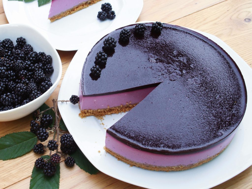 Blackberry cheesecake on a white plate on wooden table. Delicious dessert decorated with fresh fruits